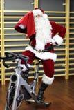 训练在锻炼脚踏车的圣诞老人在健身房 免版税图库摄影