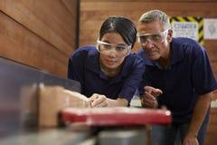 训练女性学徒的木匠使用飞机 免版税库存图片