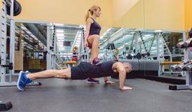 训练有坚硬俯卧撑的妇女教练一个人 免版税库存照片