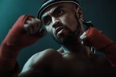 训练泰国拳击的积极的年轻泰拳拳击手特写镜头画象  库存图片