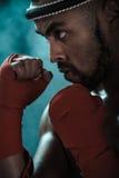 训练泰国拳击的积极的年轻泰拳拳击手特写镜头画象  图库摄影