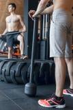 训练锻炼witth重和大轮胎和锤子室内健身中心的两个男性健身模型 免版税库存照片