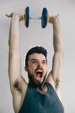 训练他的二头肌肌肉的皮包骨头的人 免版税库存照片