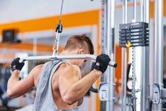 训练他的肌肉健美人在健身房 库存图片