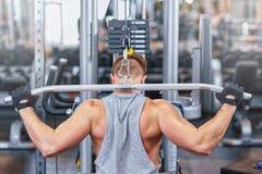 训练他的肌肉健美人在健身房 免版税库存图片