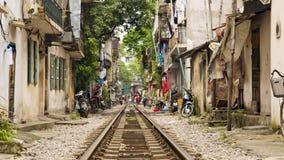 训练穿过河内贫民窟,越南街道  免版税库存照片