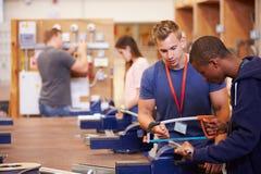 训练老师帮助的学生是电工 免版税库存照片