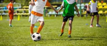 训练足球的孩子 参加足球比赛的年轻男孩 免版税图库摄影
