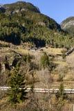 训练通过在一个晴朗的倾斜的瑞士山中的牧人小屋下在Wassen, Swit附近 图库摄影