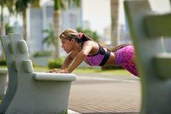 训练Pectorals的妇女做在街道长凳2的俯卧撑 库存照片