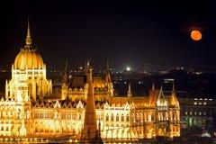议会大厦在与红色月亮,布达佩斯, Hungar的晚上 库存照片
