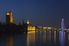 议会议院和伦敦眼在晚上 免版税图库摄影