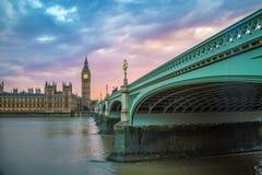 议会,伦敦,英国威斯敏斯特桥梁、大本钟和议院在日落的 免版税库存图片