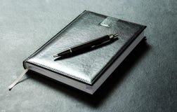 议程计划与笔的日志皮革 免版税库存图片