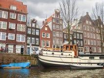 议院和小船在运河在阿姆斯特丹。 免版税库存照片