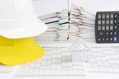 议院和白色在黄色工程师帽子在财务帐户 免版税图库摄影