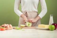议院妻子佩带的围裙做 步做烹饪苹果c 图库摄影