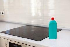 议院清洁-有洗涤剂的塑料瓶在厨房桌面 滚刀的洗涤物 归纳火炉 电火炉 库存图片