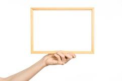 议院装饰和照片框架题目:拿着一个木画框的人的手被隔绝在白色背景在演播室 免版税库存图片