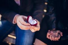 建议 人` s手拿着有圆环的一个红色礼物盒 免版税图库摄影