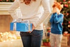 记住成熟有圣诞节礼物的夫人惊奇的矮小的儿子 免版税图库摄影