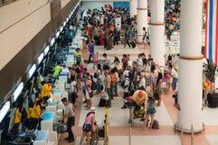 登记在报道登记柜台上国际机场的乘客 免版税库存图片