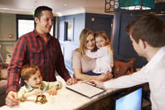 登记在旅馆总台的家庭 免版税库存照片