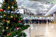 登记处柜台的圣诞树在机场和人们 免版税图库摄影