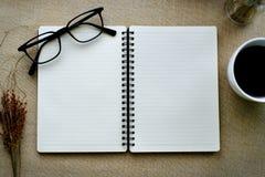记录书和镜片用咖啡在白色杯子 免版税库存照片