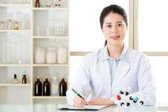 记录在剪贴板的亚裔女性科学家化学式 免版税库存照片