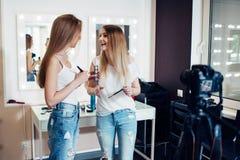 记录在照相机的两年轻女性博客作者构成讲解在美容院 免版税图库摄影