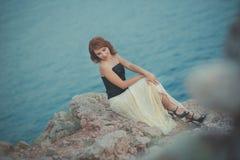 记录等候她的多岩石的海滩海角的日历红色头发女神女王/王后seamaid人海员渔夫作梦关于爱和fami 免版税库存照片