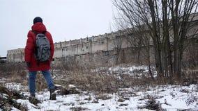 记录 有背包的男性潜随猎物者在一个被放弃的大厦附近去 股票视频