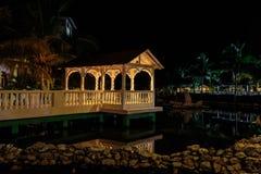 记忆Caribe与舒适眺望台的旅馆地面邀请的看法点燃了与各种各样的温暖的光,反映在水在晚上钛 免版税图库摄影