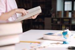 登记概念教育查出的老 读一本书的女孩在学校图书馆里  免版税图库摄影