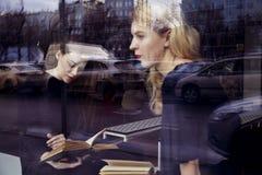 登记概念教育查出的老 两个白肤金发的女孩在窗口附近坐在图书馆里 免版税图库摄影