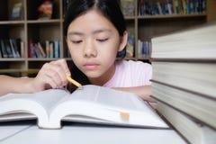 登记概念教育查出的老 女孩读书和文字在学校图书馆里  库存照片