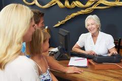 登记的旅馆接待员帮助的家庭 免版税图库摄影