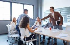 讲师与学生握手 见面在轻的背景的企业节目 概念另外现有量合伙企业编结难题二 免版税库存图片
