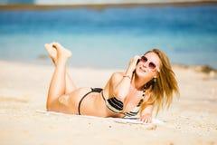 讲话的太阳镜的性感的年轻白肤金发的女孩  免版税库存照片
