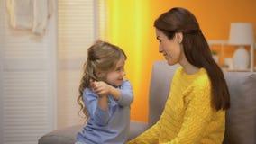 讲逗人喜爱的学龄前的女孩愉快的妈妈滑稽可笑的故事,笑和拥抱 股票视频