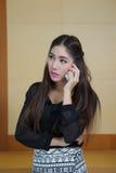 讲年轻的女商人手机 免版税库存图片