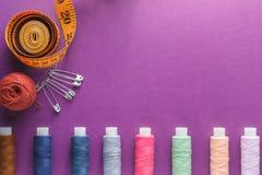 许多不同的五颜六色的缝合针线和一卷测量的磁带在紫色背景 免版税库存图片