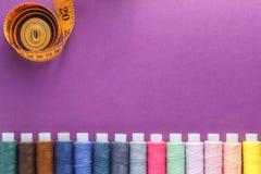 许多不同的五颜六色的缝合针线和一卷测量的磁带在紫色背景 库存图片