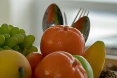 许多与一把匙子和叉子的果子堆在后面 免版税图库摄影