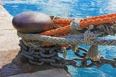 许多五颜六色的固艇索具和链子拿着靠码头的船 免版税库存照片