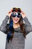 戴许多五颜六色的太阳镜的微笑的妇女 免版税库存照片