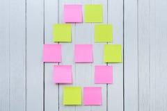 许多五颜六色的稠粘的笔记、岗位笔记或者柱子在白色木 库存图片