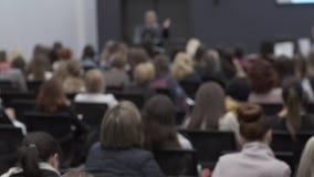 许多人民在会议听赠送者 坐在观众席的人背面图  股票录像