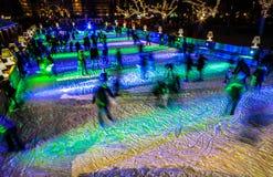 许多人民在冬天滑冰的溜冰场在Rijksmuseum前面的晚上,一个普遍的旅游目的地滑冰在阿姆斯特丹 免版税图库摄影